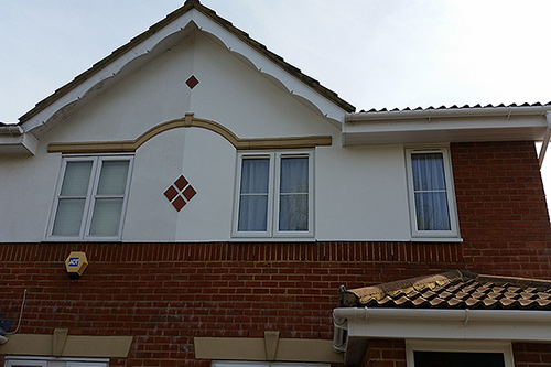 Exterior decoration to the front of house including the walls, 2 coats of exterior masonry paint, and decorative gable end, primed undercoat and a white gloss finish