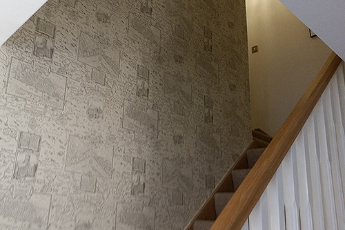 Staircase featuring designer wallpaper