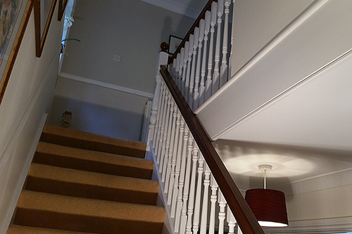 Interior decoration of staircase turning the spindles from a dark brown finish to a interior designed eggshell finish