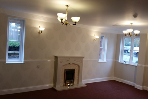 Residential communal lounge with featured fireplace wall with Laura Ashley wallpaper; walls in Farrow & Ball - works completed