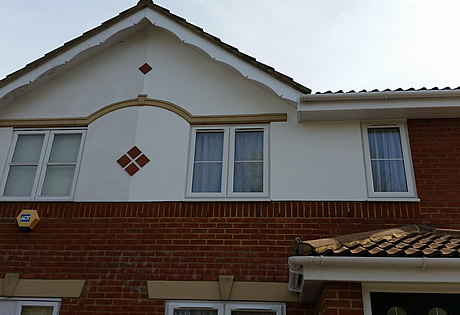 Exterior decoration to the front of house including the walls, 2 coats of exterior masonry paint, and decorative gable end, primed undercoat and a white gloss finish.